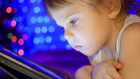 The child looks to the tablet lying on bed. In the background, lights and garlands of Christmas fir stock footage