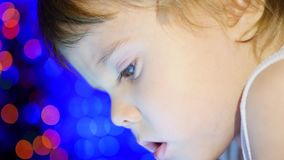 The child looks to the tablet lying on bed. In the background, lights and garlands of Christmas fir. closeup stock video