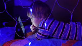 The child looks to the tablet lying on bed.On the foreground, lights garlands stock video footage