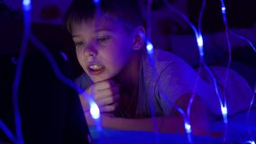 The child looks to the tablet lying on bed.On the foreground, lights garlands stock video