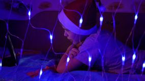 The child looks to the tablet lying on bed in hat santa.On the foreground, lights garlands stock video