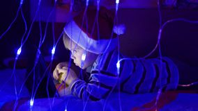 The child looks to the tablet lying on bed in hat santa.On the foreground, lights garlands stock footage