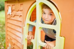 Child looks through a window in the playhouse royalty free stock photography