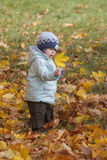 Child loos with surprise at the leaf in autumn park Stock Image