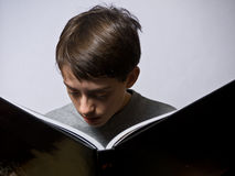 Child Lost in a large book Stock Images