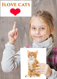 Child love cats. And points finger up Royalty Free Stock Photography