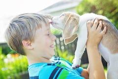 Child lovingly embraces his pet dog Stock Photos