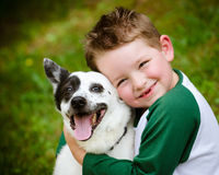 Child lovingly embraces his pet dog. A blue heeler Royalty Free Stock Images