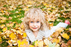 Child lying on autumn leaves Royalty Free Stock Photo