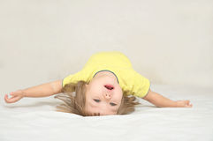 Child lying on back making arch. Little girl having fun lying on back spine, backbend, bridge figure, happy smiling child, happiness childhood concept Stock Photography