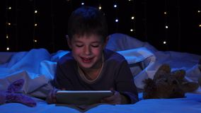 Child is lying on a bed holding a laptop and watching a cartoon. Bokeh background. Child lies on the bed with soft toys and holds a laptop in his hands and stock video