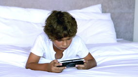 Child lying on bed. And playing a video game stock video