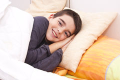 Child lying in bed Royalty Free Stock Photos