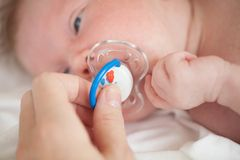 The child lying on the bed sucking on a pacifier Stock Photography