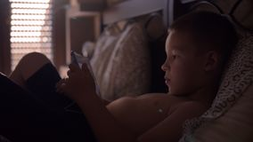Child lying in bed and watching cartoon on tablet computer. Boy spending free time at home. He relaxing in bed and watching interesting cartoon on digital tablet stock footage