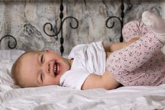 The child lies on the bed and laughs, has fun and raises his legs to the top stock image