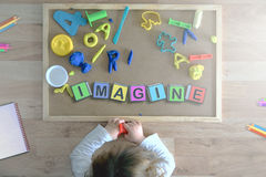 Child lying down on the floor playing with some cube letters composing the word IMAGINE. Education concept Royalty Free Stock Images