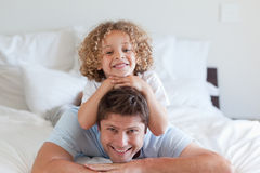 Child lying on fathers back Stock Photo