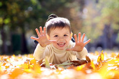 Child lying on the golden leaf Stock Image