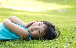 Child lying on grass. Portrait of Asian child lying on garden grass looking side Stock Photo