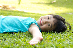 Child lying on grass. Portrait of Asian child lying on garden grass looking side Royalty Free Stock Images