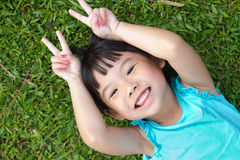 Child lying on grass. Portrait of Asian child lying on garden grass looking up Royalty Free Stock Photography