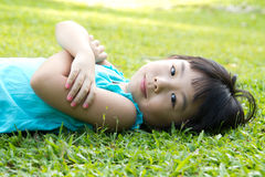 Child lying on grass. Portrait of Asian child lying on garden grass looking side Stock Photography