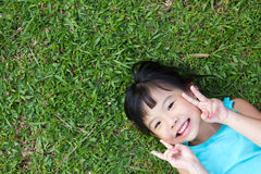 Child lying on grass. Portrait of Asian child lying on garden grass looking up Stock Image