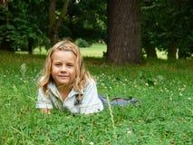 Child lying in grass Stock Photo
