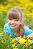Child  lying on grass in flower. Stock Image