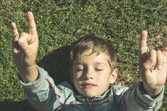 Child lying on the grass with open arms stock images