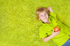 Child lying on the green carpet, holding apple. Child lying on the green carpet background, holding apple. Boy smiling and looking at camera Royalty Free Stock Photography