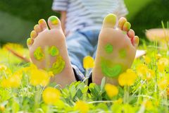 Child lying on green grass. Kid having fun outdoors in spring park. Child feet with painting smiles lying on green grass royalty free stock photos