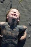 Child lying in healing mud. Child is lying in healing mud, Russia Stock Photo
