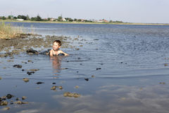 Child lying in the healthy mud Stock Image