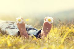 Child lying in meadow relaxing in summer sunshine Stock Photos
