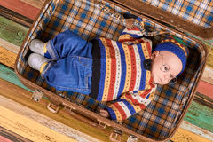 Child lying in opened suitcase. Little kid in spectacles. Tips for beginner traveler Royalty Free Stock Images