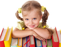 Child lying on pile of books.