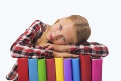 Child lying on pile of books. stock photos