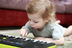 Child lying and playing on synthesizer Royalty Free Stock Image