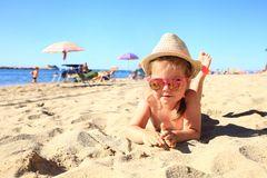 Child lying on sandy beach near blue sea. Summer vacation and healthy lifestyle concept. Stock Photography