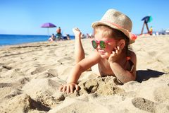 Child lying on sandy beach near blue sea. Summer vacation and healthy lifestyle concept. Royalty Free Stock Photo