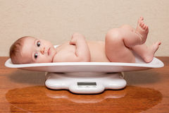 Child is lying on scales Stock Photos