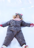 Child lying on the snow and playing in winter Royalty Free Stock Images