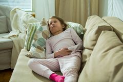 Child lying on sofa in the living room with stomach pain stock photos