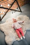 The child is lying on a woolen carpet and smiles at the camera royalty free stock photos