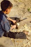 Child and machete. This child of the Hmong and the process of making a top. He deftly wields the machete to his young age. One can not help but be Stock Photo
