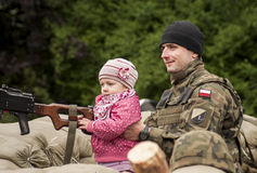Child with machine gun. Szczecin, Poland - Mai 29, 2014: Veterans Day in Poland. Unidentified soldier with his daughter.Child holds the hand machine gun Stock Images