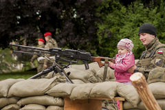 Child with machine gun. Szczecin, Poland - Mai 29, 2014: Veterans Day in Poland. Unidentified soldier with his daughter.Child holds the hand machine gun Royalty Free Stock Photo