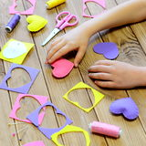 Child made hearts out of felt. Children`s hands on the table. Handmade Valentines day heart gifts, crafts materials and tools Royalty Free Stock Images